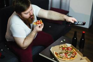 Fat man eats pizza sitting on the sofa