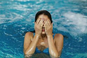 Girl covering her eyes in the pool