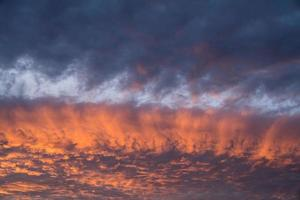 Streaks of golden sunlight across the clouds