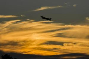 Airplane over golden hour sunset
