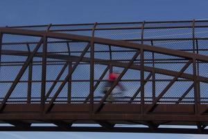 Cyclist in motion crossing bridge