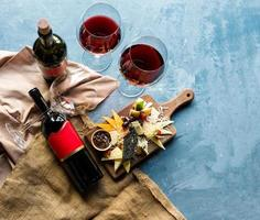 Wine bottle and glasses with mix of cheese photo