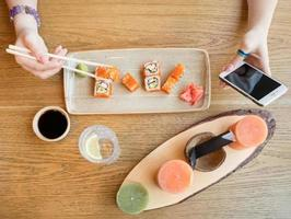 Woman eating sushi and using smartphone, top view