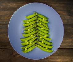 Green peas in the form of a Christmas tree on a plate