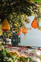Hallstatt, Australia, 2020 - Orange pendant lamps in a tree at a cafe