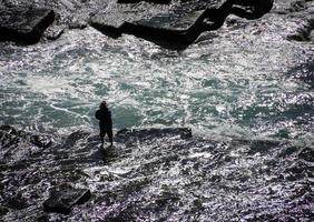 Sydney, Australia, 2020 - Man fishing while wading in the water