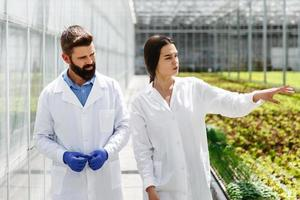 Two researchers in laboratory robes walk around the greenhouse