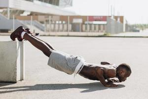 African American man does pus-ups on the street during his morning work-out