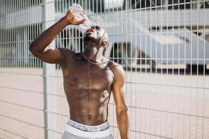 Fit black man drinking water