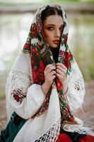 Beautiful girl in a traditional ethnic dress with an embroidered shawl