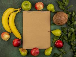 Assorted fruit around note pad on green background