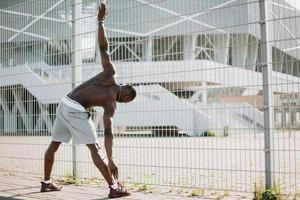 Man stretching near a fence