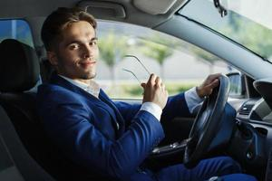 Handsome young businessman sits at the steering wheel inside the car