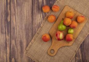 Surtido de frutas sobre tabla de cortar sobre fondo de madera foto