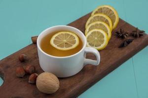 Taza de té con rodajas de limón y nueces sobre fondo azul.