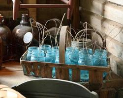 Blue glass jars on brown wooden basket photo