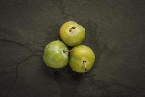 Three greengages on slate photo