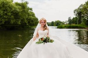 bride in a white boat on the lake photo