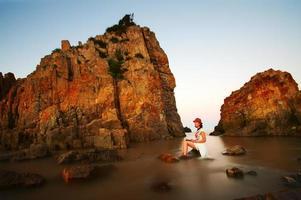 Young beautiful woman relaxing on rocky coast?