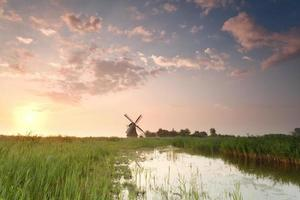 sunrise over windmill by river photo