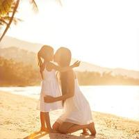 mother and dauther in beachat sunsat, happy photo