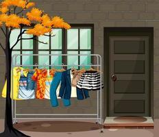 Mucha ropa colgada en un perchero frente a la escena de la casa. vector