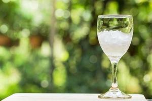 Glass filled with ice on nature background