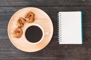Top view of coffee and cookies with a notebook
