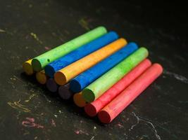 Stacked colorful chalk on dark background