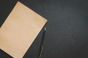 Bloc de notas y bolígrafo marrón sobre un escritorio negro