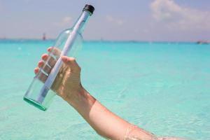 persona sosteniendo una botella de vidrio con un mensaje
