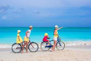 Family riding bikes on a beach