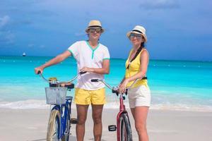 Feliz pareja con bicicletas en una playa de arena blanca