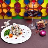 Tasty salad and red wine with colorful background