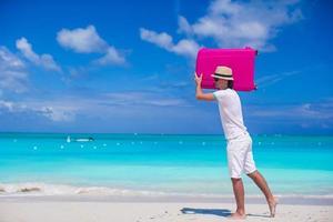 Hombre acarreando una maleta en la playa