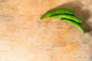 Green chillis on wooden background