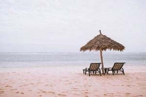Two lounge chairs and an umbrella at a beach photo