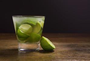 A caipirinha cocktail on a wood table