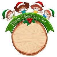 Blank wooden board with Merry Christmas 2020 font logo and children wear mask