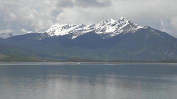 Boote segeln auf See unter felsigen Bergen 4k video