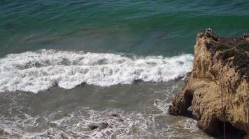 Primer plano de las olas rompiendo contra la costa rocosa de California 4k