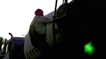 trabalhador da construção civil escalando em um caminhão de cimento 4k video estoque