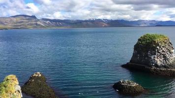Escena costera de Islandia con agua del océano y montañas 4k