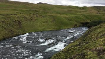 Corriente de agua de Islandia en la cima de las montañas verdes 4k video
