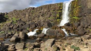 cachoeira caindo sobre rochas na Islândia 4k