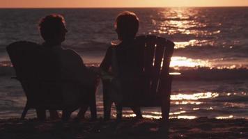 um casal senta e vê o pôr do sol