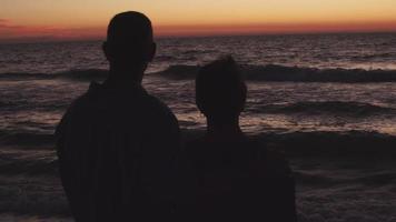um casal vê o pôr do sol juntos na praia