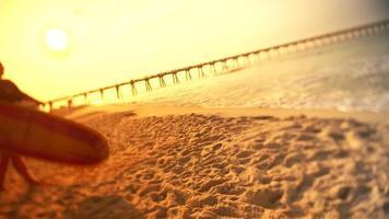 um surfista desce para a praia ao pôr do sol