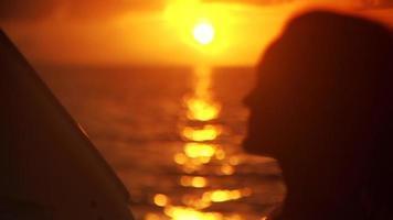 água do oceano e rosto de mulher ao pôr do sol