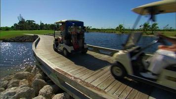 carrinhos de golfe passam pela ponte